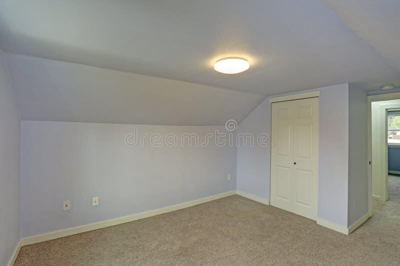 Pequeño dormitorio azul vacío acentuado con el techo saltado fotos de archivo