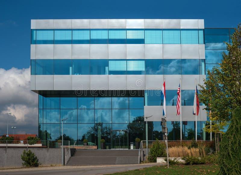 Pequeño edificio de oficinas suburbano Vidrio y concreto Delante de la entrada son las astas de bandera Vidrios del azul imagen de archivo