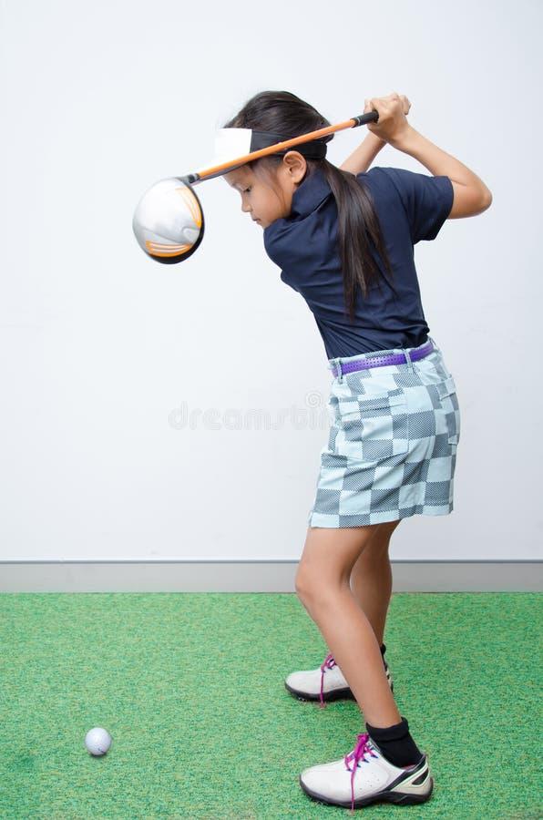 Pequeño entrenamiento asiático del club de golf del takine de la muchacha imagenes de archivo