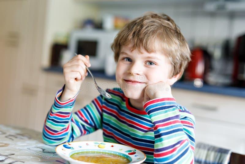 Pequeño escolar adorable que come la sopa de verduras interior fotos de archivo libres de regalías