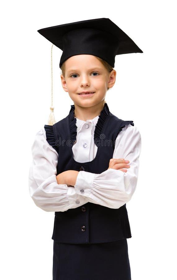 Pequeño estudiante en casquillo académico con las manos cruzadas fotografía de archivo