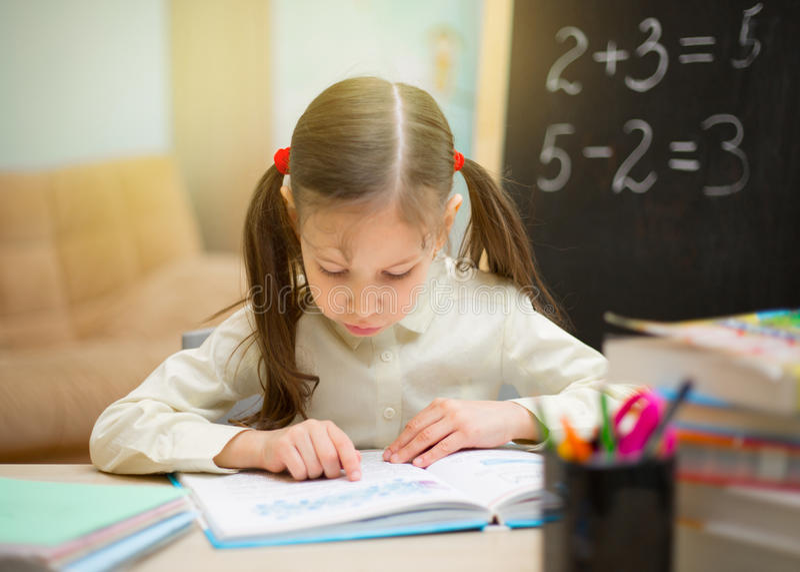 Pequeño estudiante La chica joven hermosa está enseñando en casa en blac fotos de archivo libres de regalías