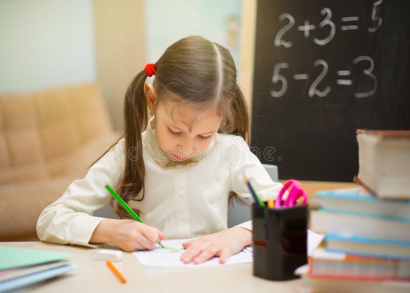 Pequeño estudiante La chica joven hermosa está enseñando en casa en blac imágenes de archivo libres de regalías