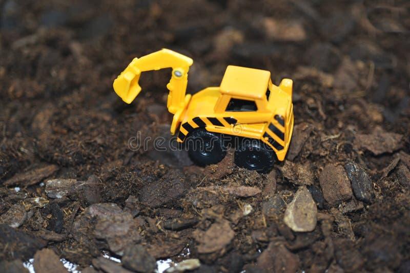 Pequeño excavador decorativo en la tierra foto de archivo