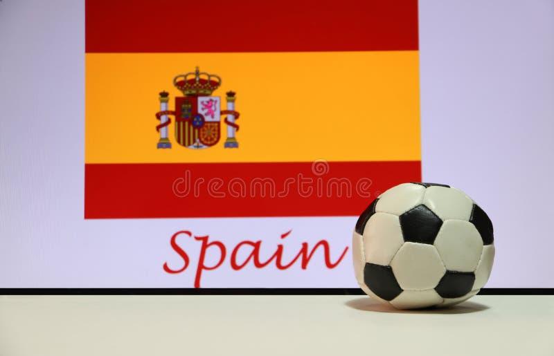 Pequeño fútbol en el piso blanco y la bandera española de la nación con el texto del fondo de España imagen de archivo
