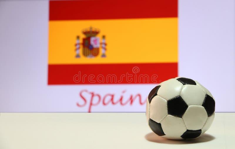 Pequeño fútbol en el piso blanco y la bandera española de la nación con el texto del fondo de España fotos de archivo