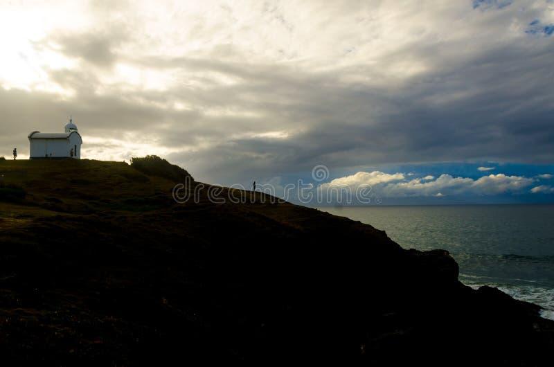 Pequeño faro encima de la colina durante salida del sol de la mañana imagen de archivo