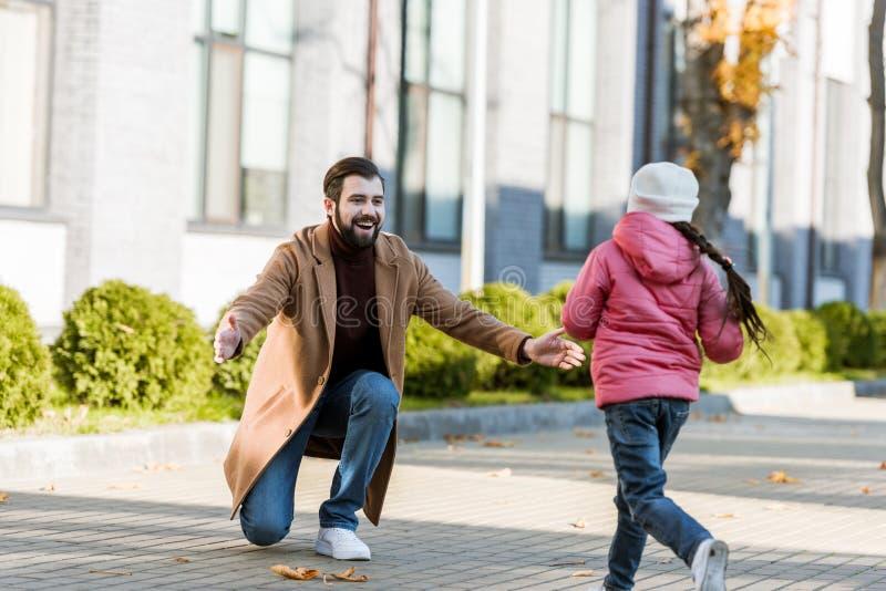 pequeño funcionamiento de la hija para abrazar a su padre feliz imágenes de archivo libres de regalías
