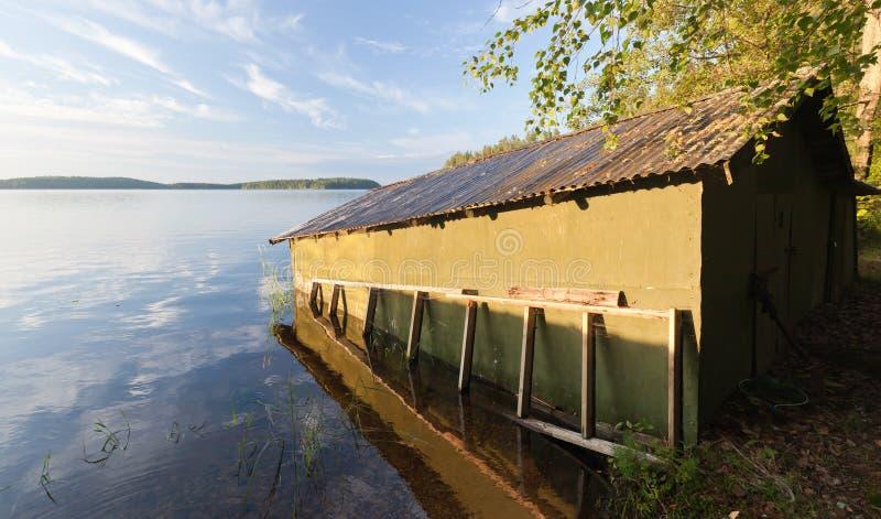 Pequeño garage de madera verde del barco en la costa fotografía de archivo libre de regalías