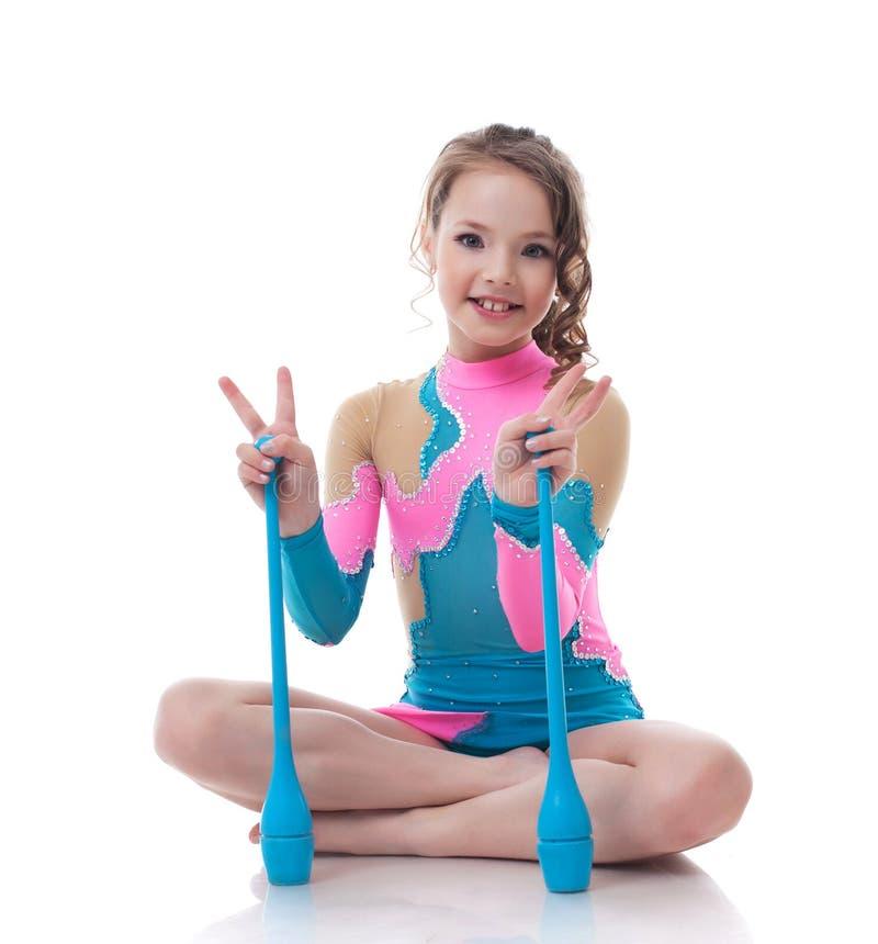 Pequeño gimnasta alegre que presenta con macis foto de archivo libre de regalías