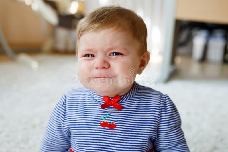 Pequeño griterío triste lindo del bebé Niño hambriento o cansado que se sienta dentro y que tiene rasgones imagenes de archivo