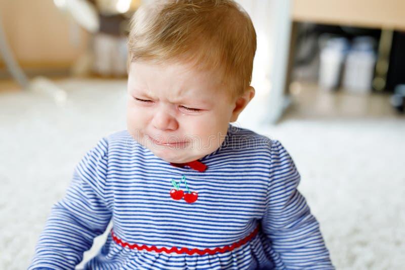 Pequeño griterío triste lindo del bebé Niño hambriento o cansado que se sienta dentro y que tiene rasgones imagen de archivo