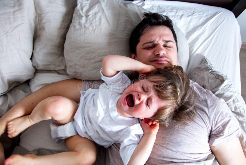 Pequeño grito del bebé en un padre cuando él no quiere despertar imagenes de archivo