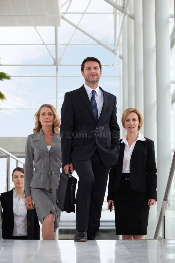 Pequeño grupo de ejecutivos que recorren encima de las escaleras foto de archivo libre de regalías
