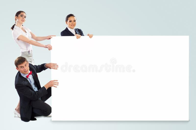 Pequeño grupo de personas que sostiene una bandera en blanco imagen de archivo