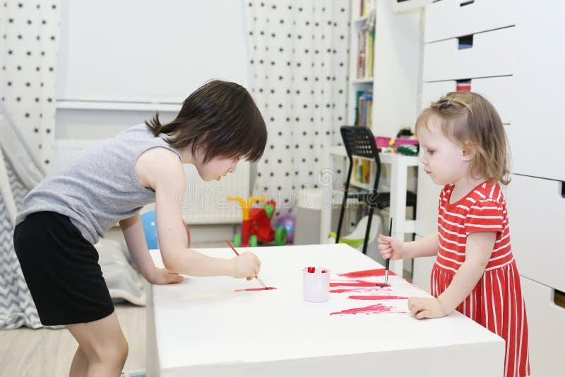 Pequeño hermano 5 años y hermanas 2 años que pintan en casa fotografía de archivo
