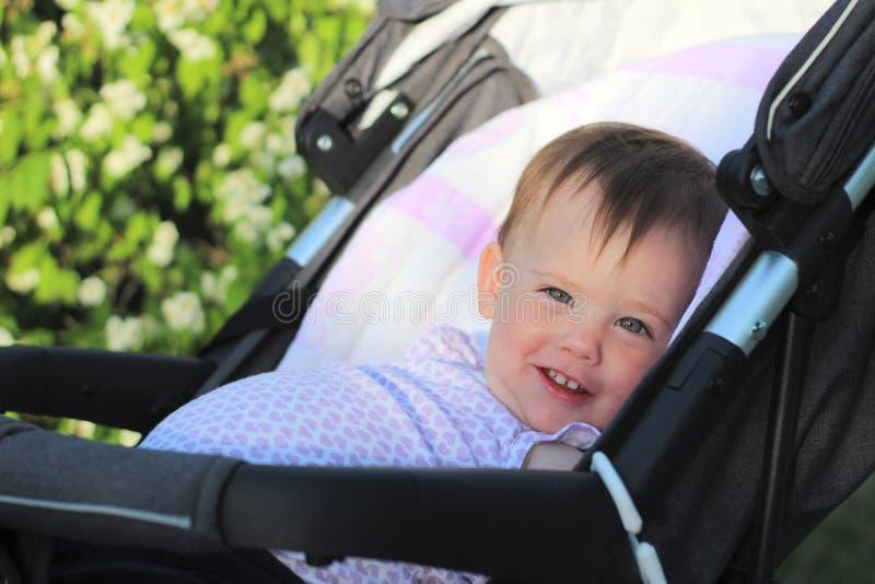pequeño, hermoso, sonriendo, bebé lindo del pelirrojo en hacia fuera-de-puertas de un cochecito de niño en una camisa sin mangas  fotos de archivo libres de regalías
