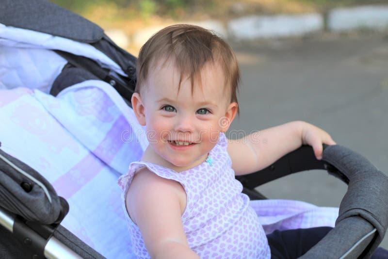 pequeño, hermoso, sonriendo, el bebé lindo del pelirrojo en una camisa sin mangas en hacia fuera-de-puertas de un cochecito de ni foto de archivo