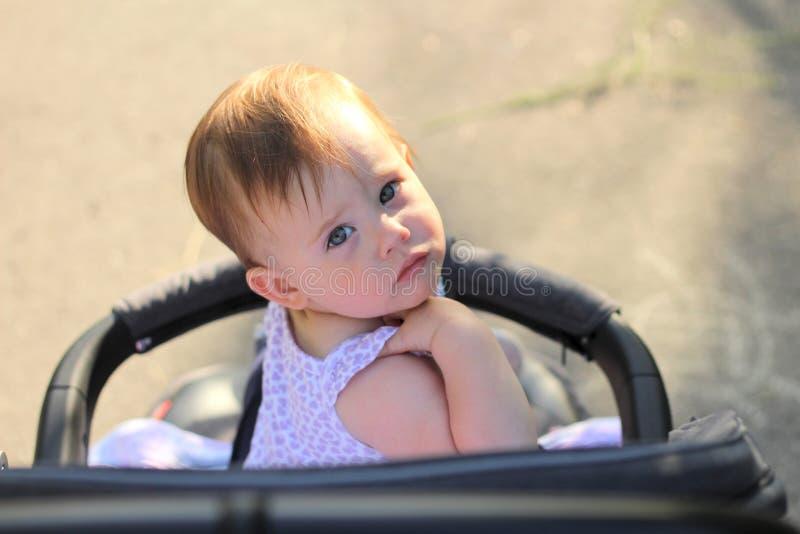 pequeño, hermoso, sonriendo, el bebé lindo del pelirrojo en una camisa sin mangas en hacia fuera-de-puertas de un cochecito de ni fotografía de archivo libre de regalías