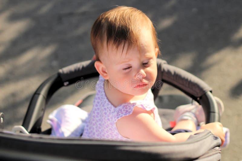 pequeño, hermoso, sonriendo, el bebé lindo del pelirrojo en una camisa sin mangas en hacia fuera-de-puertas de un cochecito de ni fotos de archivo libres de regalías