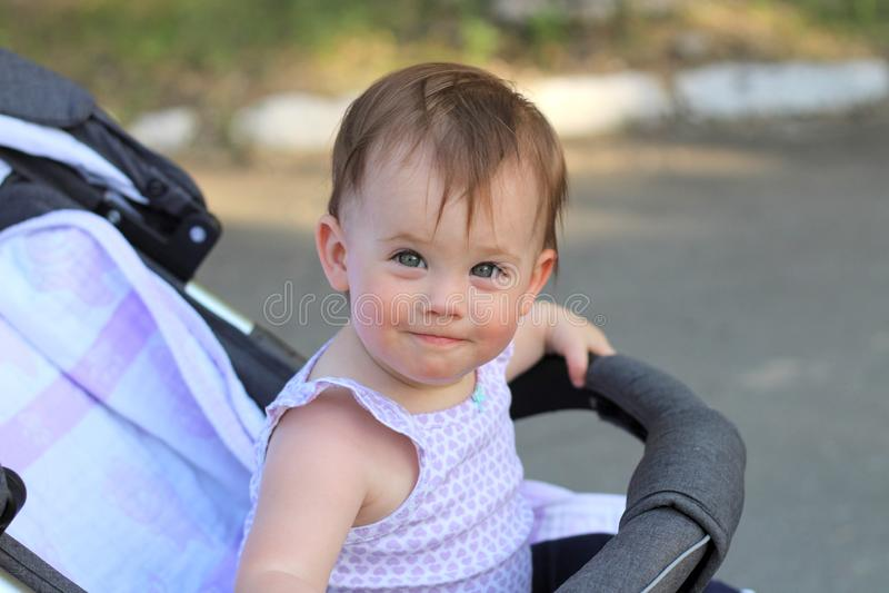 pequeño, hermoso, sonriendo, el bebé lindo del pelirrojo en una camisa sin mangas en hacia fuera-de-puertas de un cochecito de ni fotografía de archivo