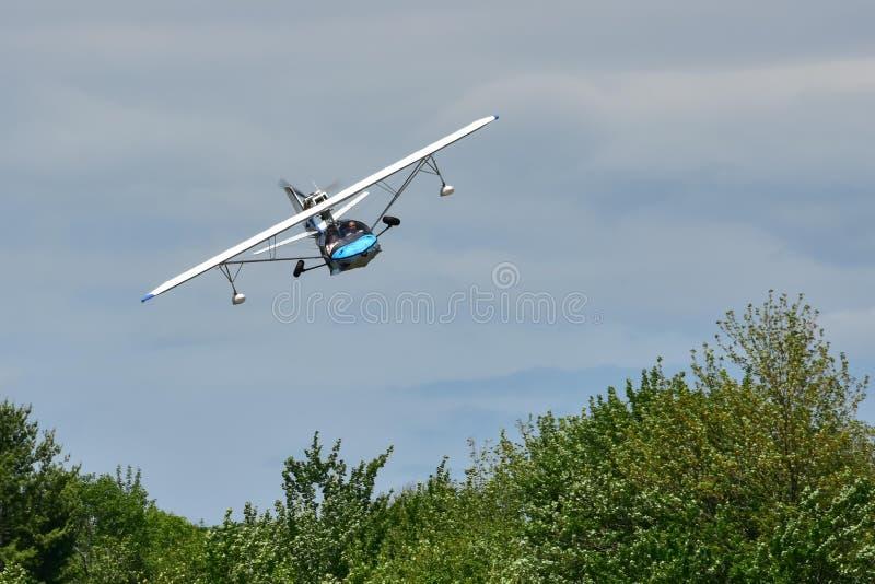 Pequeño hidroavión en vuelo bajo sobre árboles imagenes de archivo