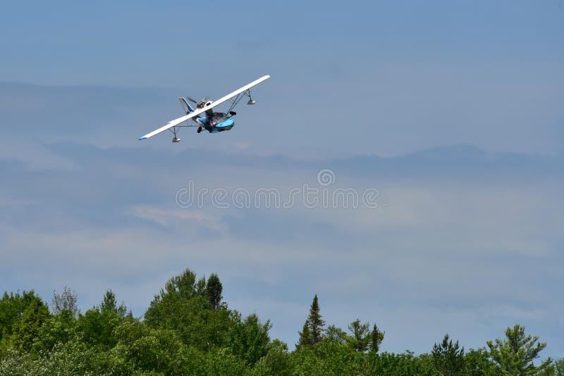 Pequeño hidroavión en vuelo bajo sobre los árboles 2 imágenes de archivo libres de regalías