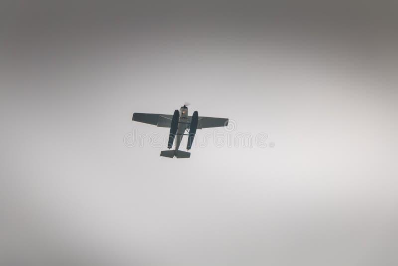 Pequeño hidroavión que está a punto de aterrizar en el lago Como imagen de archivo