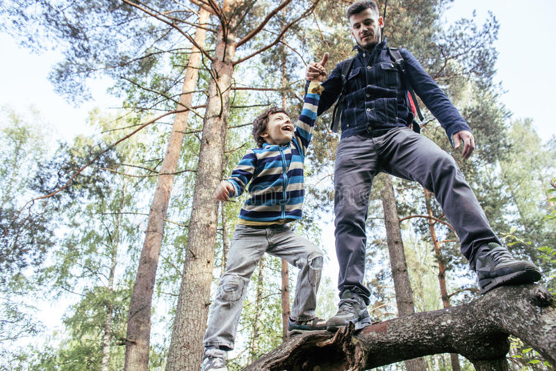 Pequeño hijo con el padre que sube en árbol junto en el bosque, concepto de la gente de la forma de vida, familia sonriente feliz foto de archivo libre de regalías