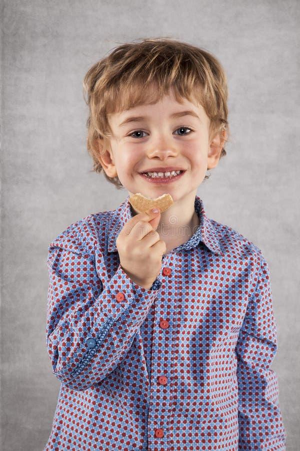 Pequeño hombre de negocios con una sonrisa en sus bocas que come las galletas imágenes de archivo libres de regalías