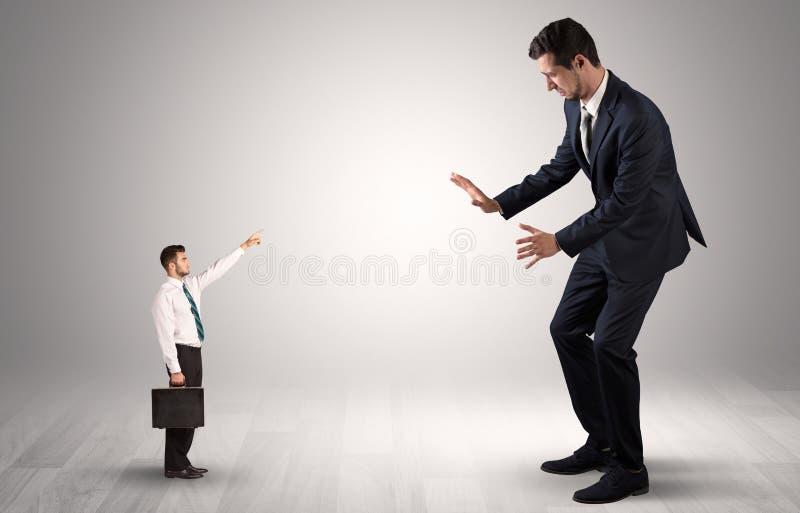 Pequeño hombre de negocios que señala a un hombre de negocios gigante imagen de archivo libre de regalías