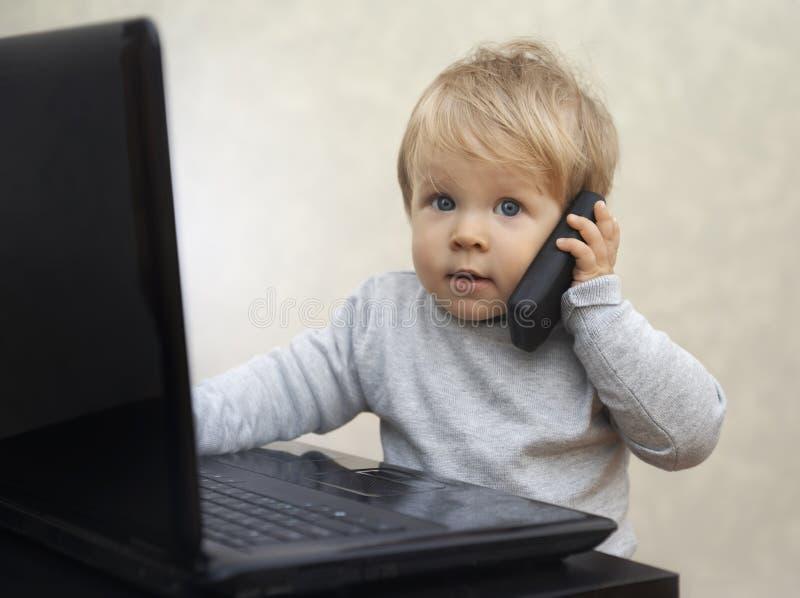 Pequeño hombre de negocios que se sienta en el ordenador con un teléfono celular del juguete fotos de archivo