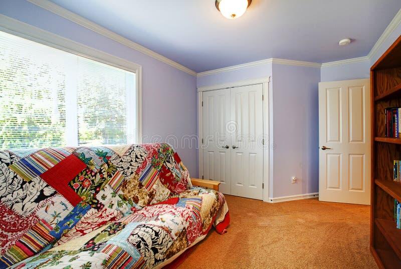 Pequeño interior de la sala de estar con las paredes y la moqueta purpúreas claras imagenes de archivo