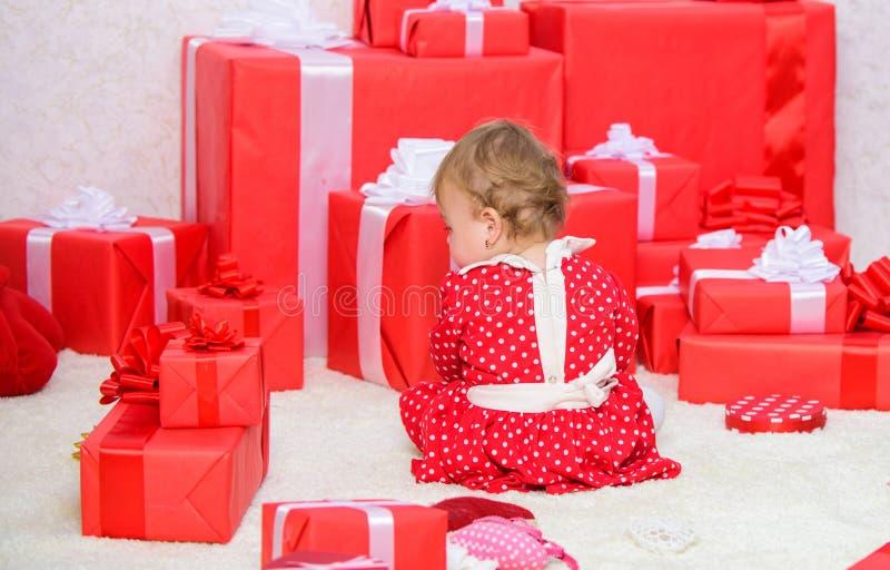 Pequeño juego del bebé cerca de la pila de cajas de regalo rojas envueltas La mi primera Navidad Distribución de la alegría de la foto de archivo