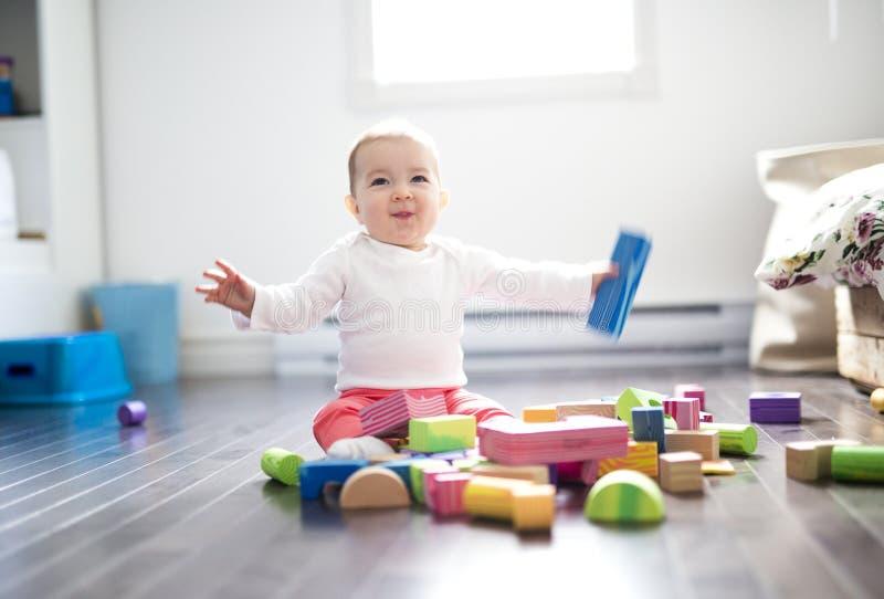 Pequeño juego lindo del bebé con los ladrillos plásticos que se sientan dentro en un piso de tejas imagen de archivo