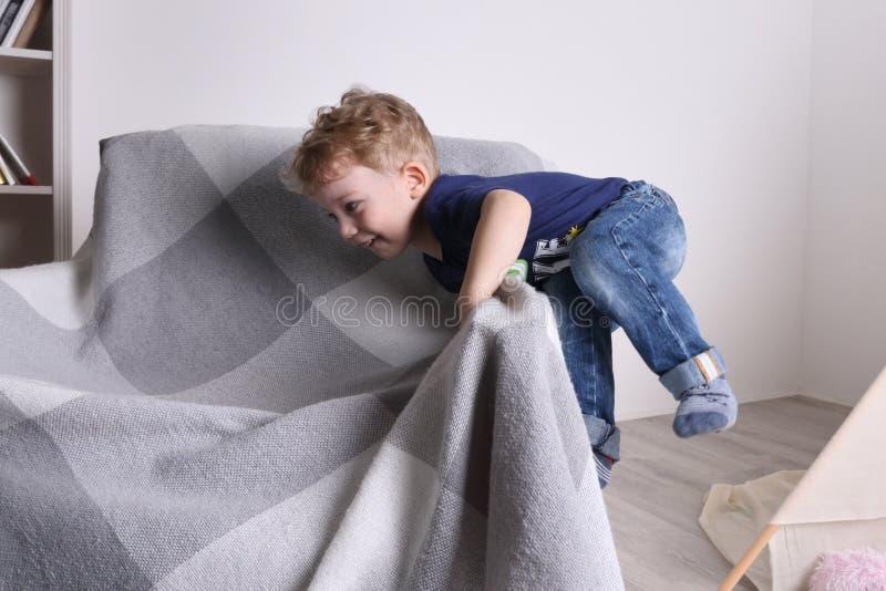 Pequeño juego lindo feliz del muchacho en la butaca en sala de estar foto de archivo