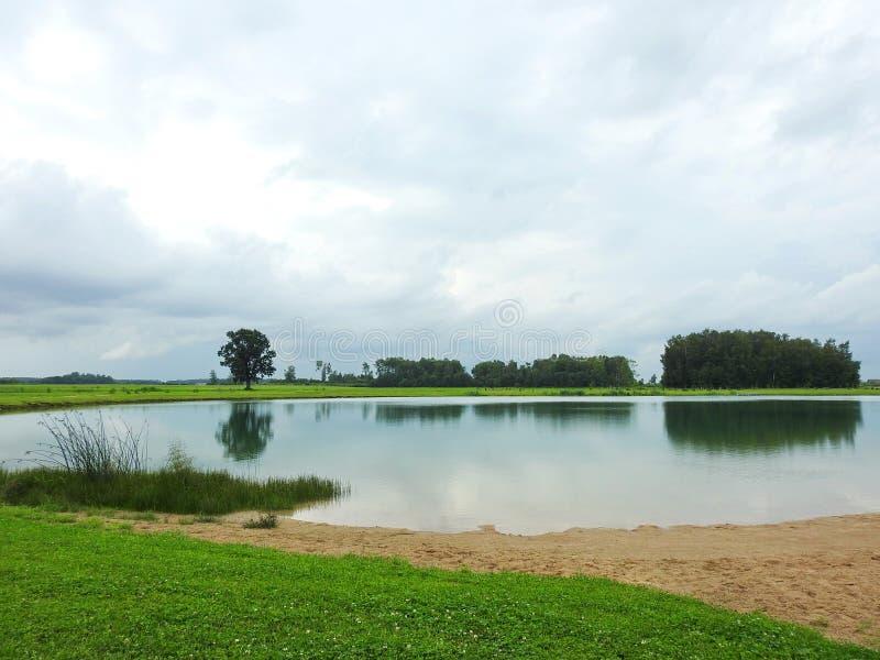 Pequeño lago, árboles y cielo nublado hermoso, Lituania imagenes de archivo