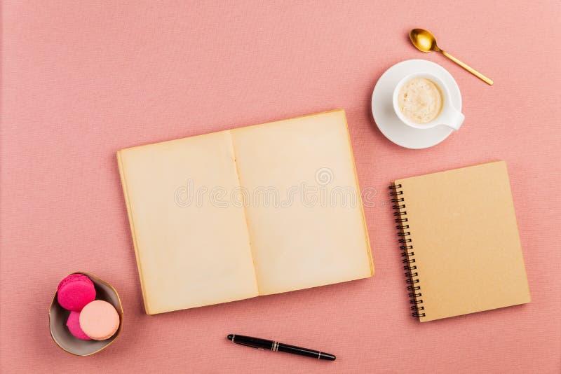 Pequeño libro antiguo vacío abierto con los macarrones franceses rosados en el lado, la taza de café, la cuchara de oro y el cuad fotos de archivo libres de regalías
