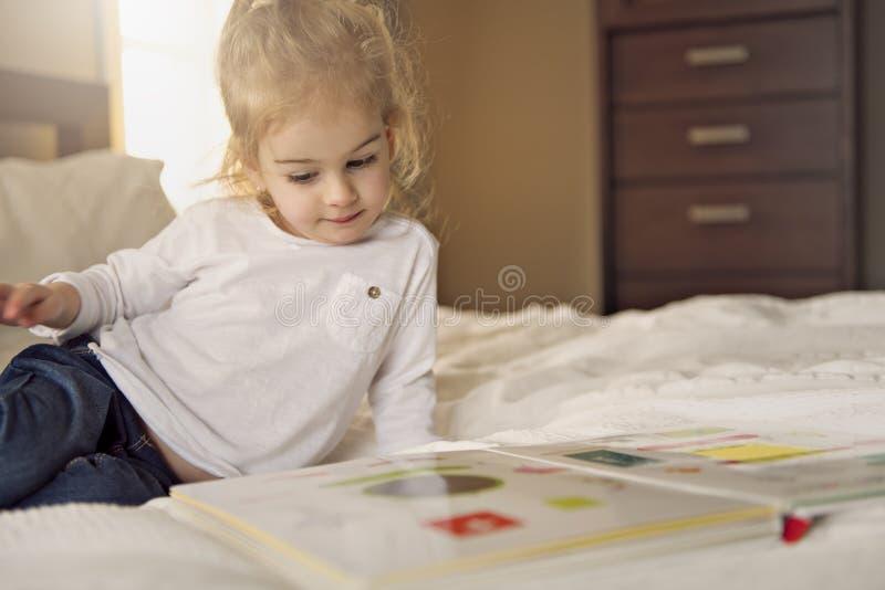 Pequeño libro de lectura lindo de la muchacha en cama imágenes de archivo libres de regalías