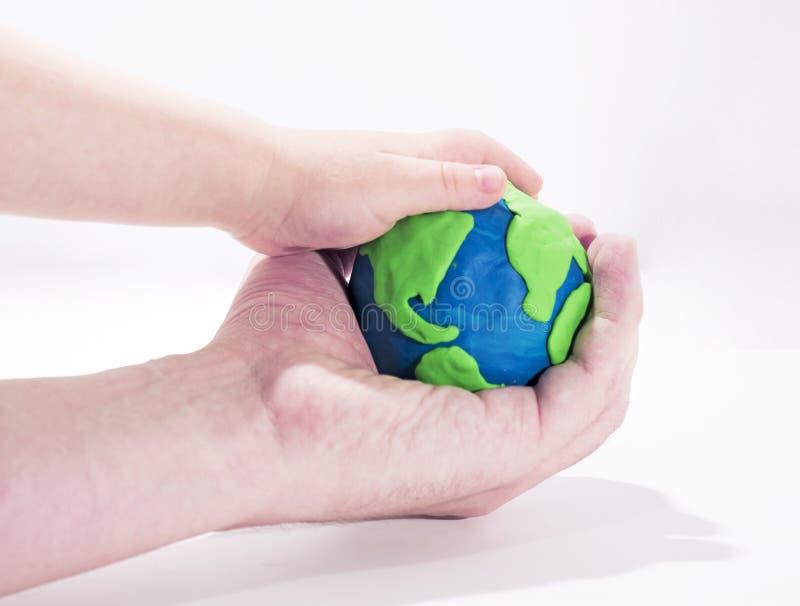 Pequeño modelo de tierra con las manos humanas imagen de archivo libre de regalías