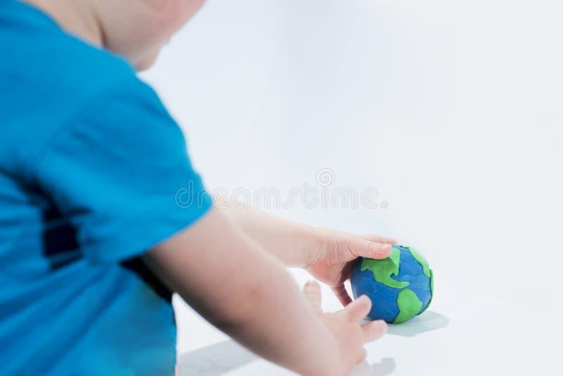 Pequeño modelo de tierra con las manos humanas imagenes de archivo