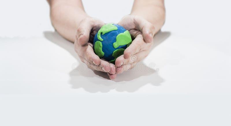 Pequeño modelo de tierra con las manos humanas foto de archivo libre de regalías