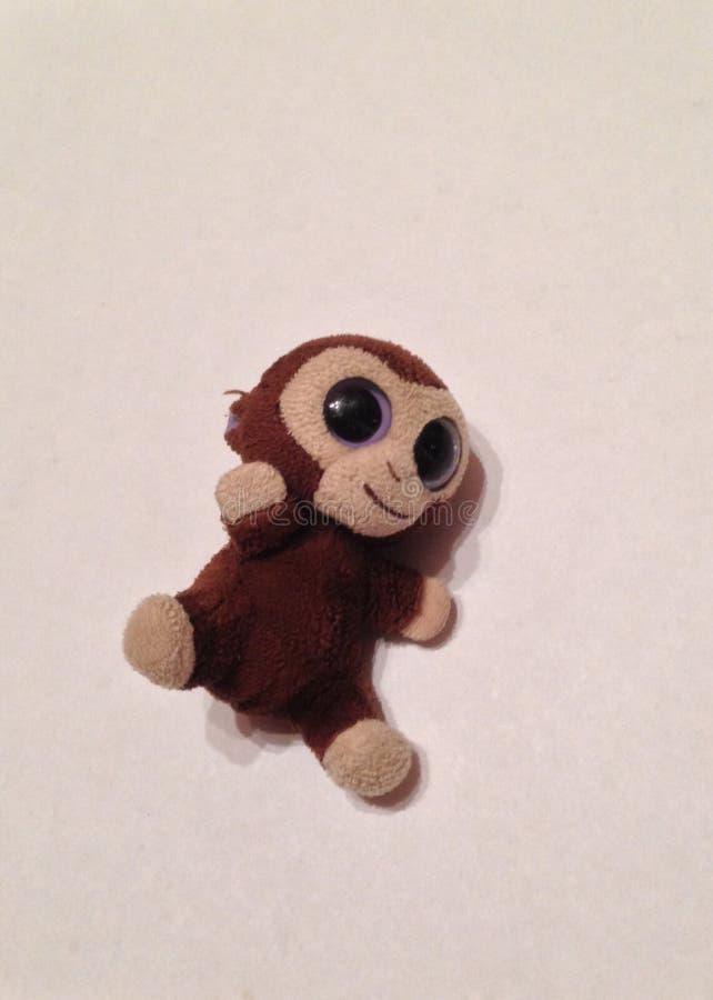 Pequeño mono relleno en un fondo blanco imagenes de archivo