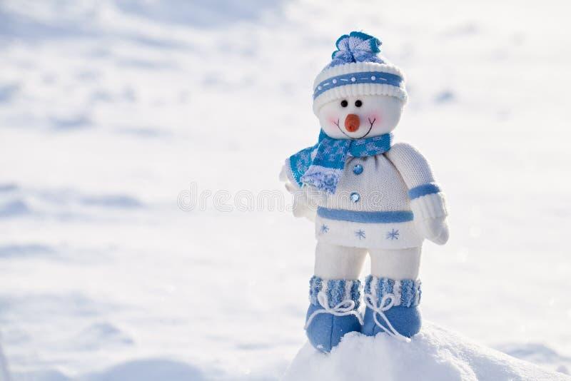 Pequeño muñeco de nieve con la nariz de la zanahoria en la nieve imagen de archivo