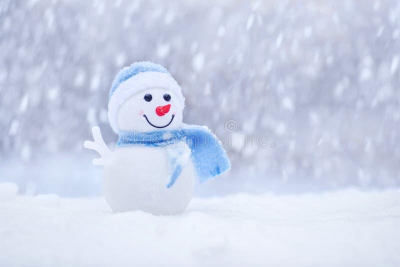 Pequeño muñeco de nieve en un casquillo y una bufanda en nieve en el invierno Muñeco de nieve feliz con la bola de nieve Tarjeta  foto de archivo