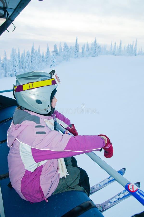 Pequeño muchacha-esquiador en la elevación de esquí imagen de archivo libre de regalías