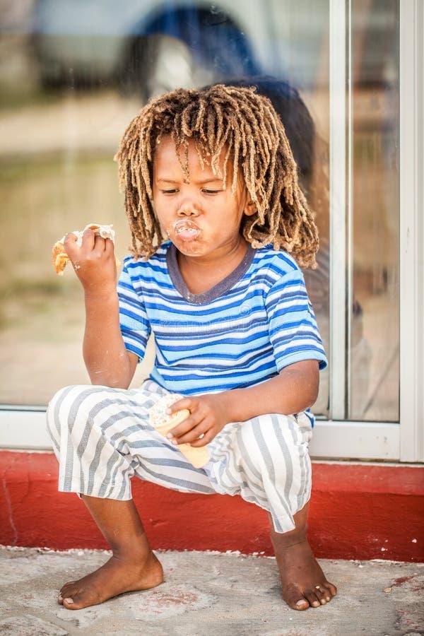 Pequeño muchacho africano que come el pan foto de archivo libre de regalías