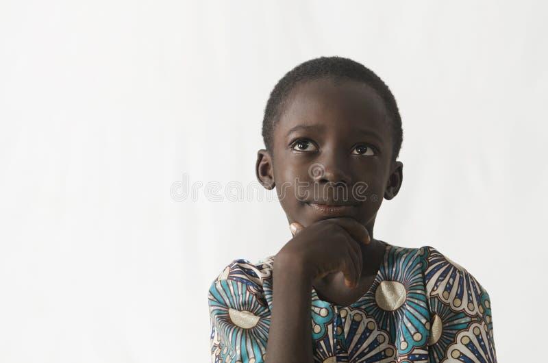 Pequeño muchacho africano que piensa en su futuro, aislado en blanco imagen de archivo libre de regalías