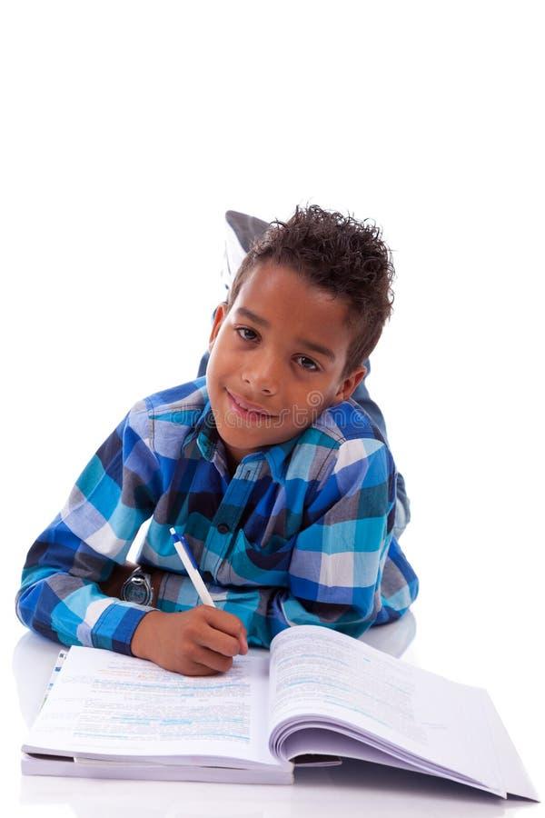 Pequeño muchacho africano que se acuesta en el libro del suelo y de lectura fotos de archivo
