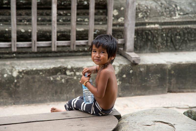 Pequeño muchacho asiático con la botella de agua que presenta en el templ de Angkor Wat imágenes de archivo libres de regalías